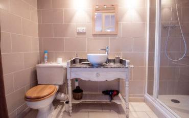 une grande salle d'eau avec une grande douche esprit brocante