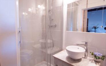 une grande douche et une vasque sur meuble de toilette patiné